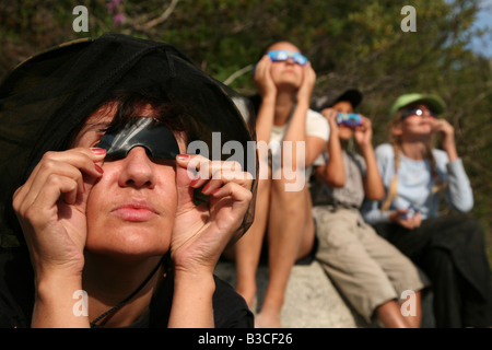 People watching a total solar eclipse through the floppy disk on August 1, 2008, in the Altai Mountains, Russia - Stock Photo