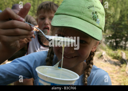 Young girl eating the spoon of condensed milk during a trekking in the Altai Mountains, Russia - Stock Photo