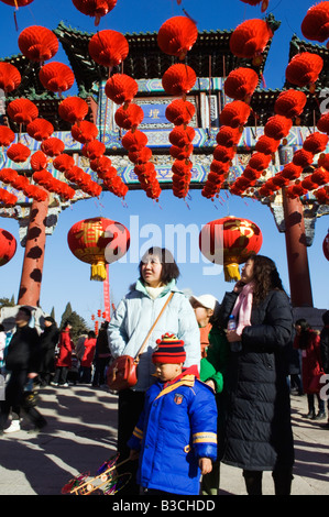 China, Beijing. Chinese New Year Spring Festival - A family under red lantern decorations at Ditan Park temple fair.