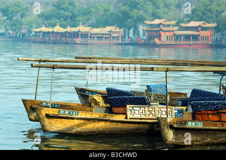 China, Zhejiang Province, Hangzhou. Boats and temple pavilions on the edge of West Lake - Stock Photo