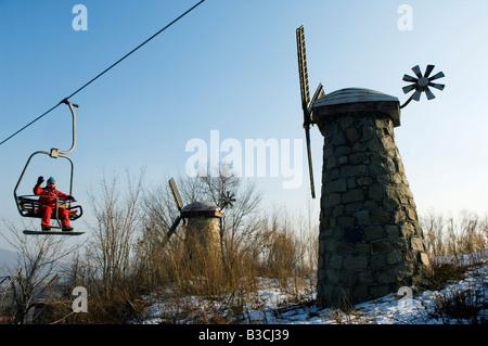China, Northeast China, Heilongjiang Province, Yabuli ski resort. A chair lift takes skiers and snowboarders up - Stock Photo
