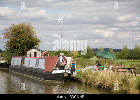 a narrowboat at a residential mooring on the Grand Union canal near Tring with its own wind turbine electricity - Stock Photo