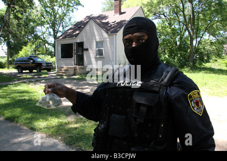 Detroit Narcotics police officer holding a bag of cannabis found during a drugs raid - Stock Photo