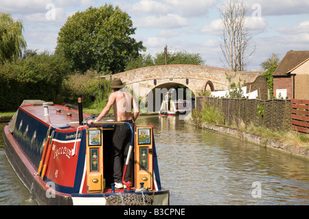 narrowboats going under a bridge on the Grand Union Canal near Tring in Hertfordshire UK - Stock Photo