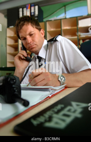 A SECURITY GUARD ANSWERS A PHONECALL AND MAKES AN ENTRY IN A LOG BOOK UK - Stock Photo