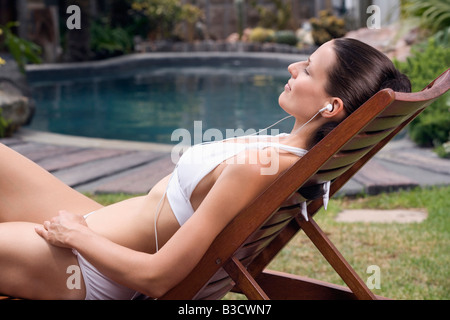 Young woman in deck chair listening to MP3-Player, portrait - Stock Photo