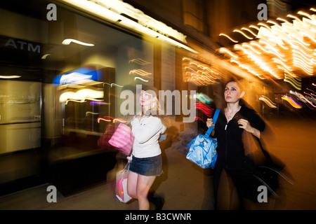 Young women carrying shopping bags - Stock Photo