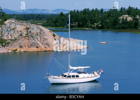 Sailboat moored on the turquoise water of Thirty Thousand Islands in Georgian Bay Ontario - Stock Photo
