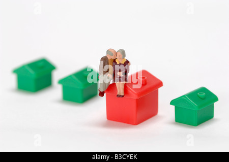 Plastic figurines sitting on roof of toy house - Stock Photo