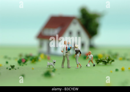 Plastic figurines in front of house - Stock Photo