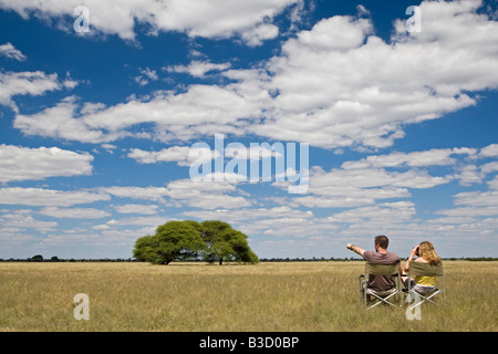 Africa, Botswana, Tourists looking at the landscape - Stock Photo