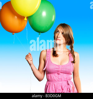 Teenage girl (16-17) holding bunch of balloons, portrait - Stock Photo