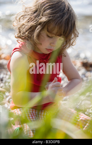 Germany, Bavaria, Ammersee, little girl (3-4) playing on beach - Stock Photo