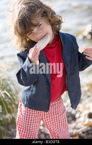 Germany, Bavaria, Ammersee, little girl (3-4) eating bread