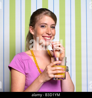 Teenage girl (16-17) drinking orange juice, portrait - Stock Photo