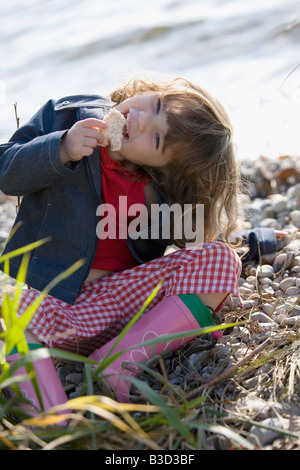 Germany, Bavaria, Ammersee, little girl (3-4), eating bread