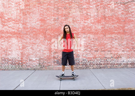 Young man standing on skateboard, portrait - Stock Photo