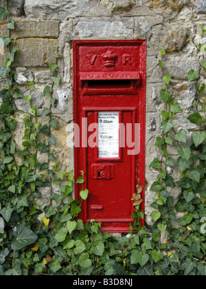 Old Victorian red painted mail postbox in a wall in Dorset UK - Stock Photo