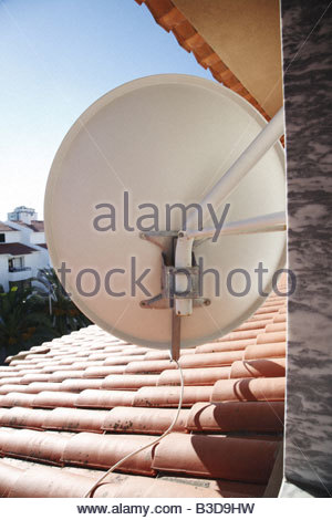 TV satellite dish fixed to outside of building - Stock Photo