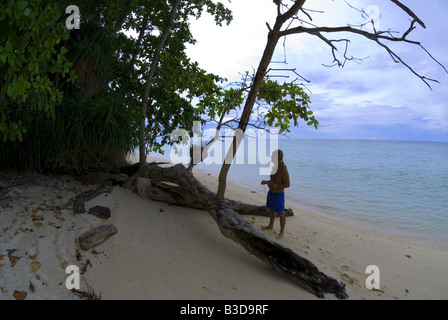 Young male watching tropical jungle trees on a dream island - Stock Photo