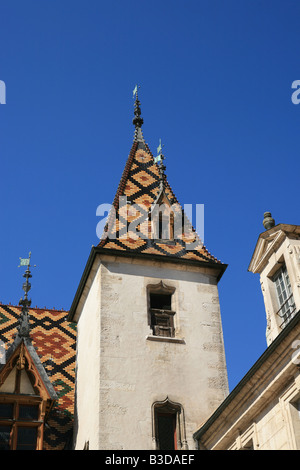 Superb Burgundian roof tiles on the tower of the Hospice Hotel-Dieu in Beaune Burgundy France Europe - Stock Photo
