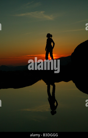 Girl reflected in a lake at sunset, at Litlefjellet, Romsdalen, Rauma kommune, Norway. - Stock Photo