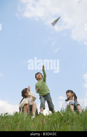 Boy throwing paper airplane while girls sitting beside - Stock Photo