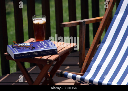 Reading Bill Bryson s travel book on the deck in summer - Stock Photo