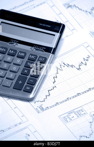 Calculator laying on stock market, market graph, graphs, chart, charts - Stock Photo