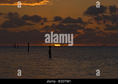 Round orange sun rising out of ocean into low clouds, orange red sky and orange reflections on upper clouds Key - Stock Photo