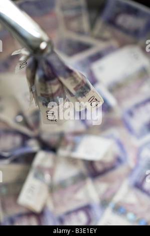 Pouring money down the drain concept - Stock Photo