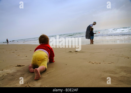 A baby girl , dressed in a colorfull sweater, crawls toward her sister and mother as they play on the beach. - Stock Photo