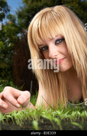 young blonde haired woman late teens early twenties tending a tray of parsley herb seedlings in a garden - Stock Photo