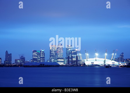 Canary Wharf skyline and O2 Millennium dome arena at dusk on the River Thames in London England UK - Stock Photo