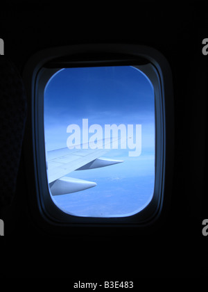 Looking out an airplane's cabin window with a view of the wing and blue sky - Stock Photo