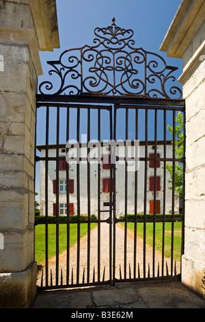 A large impressive Basque house behind its tall wrought iron gate (France). Maison basque derrière un grand portail - Stock Photo