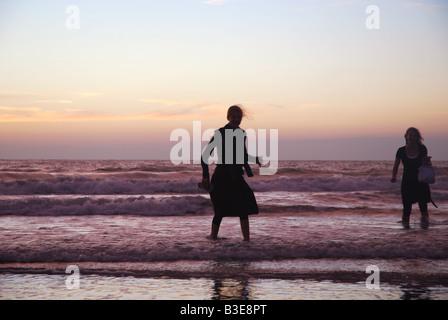 beach scenebeach scene with silhouette of teenage girls at sunset - Stock Photo