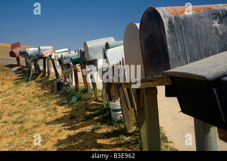 Row of mailboxes in the rural Central Valley of California USA against a deep blue sky - Stock Photo