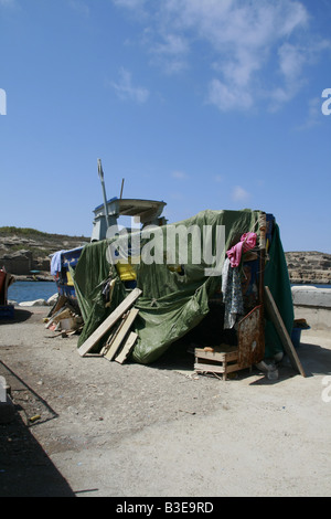 old fishing boat with tarpaulin cover on dry land in sun - Stock Photo