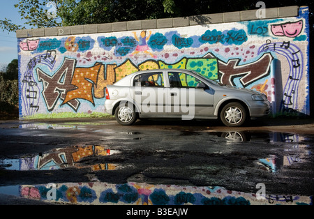 Car and graffiti wall reflected in puddles. - Stock Photo