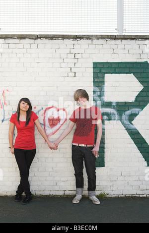 Teenage couple holding hands - Stock Photo