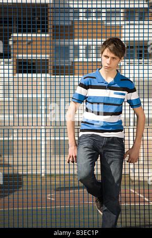 Boy leaning on fence - Stock Photo