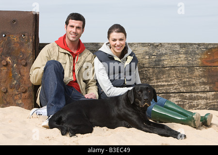 Couple sitting with pet dog at beach - Stock Photo