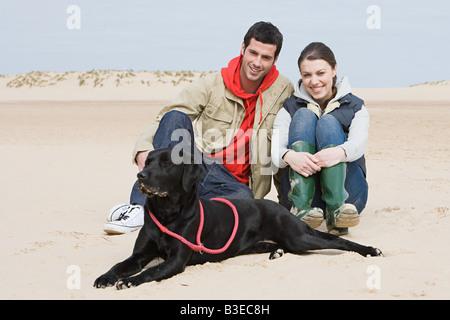Couple sitting on beach with pet dog - Stock Photo