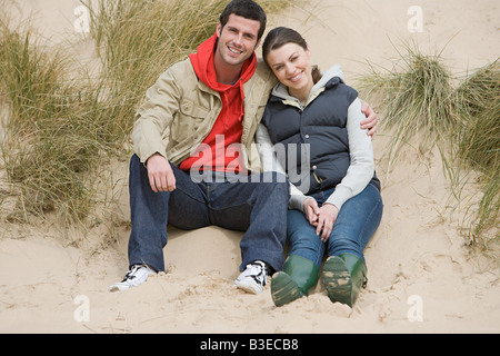 Couple sitting on a sand dune - Stock Photo