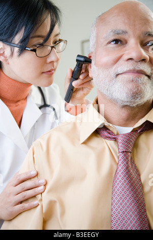 A doctor examining a patients ear - Stock Photo