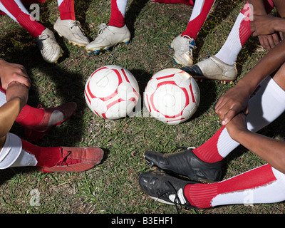 Footballs and legs of footballers - Stock Photo