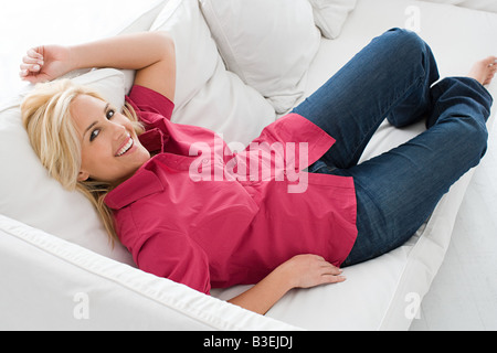 Portrait of a woman reclining on a sofa - Stock Photo