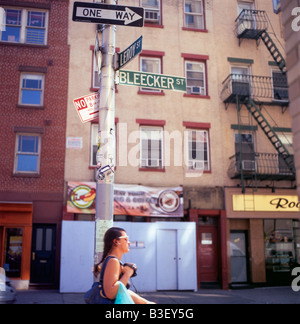 A young woman wearing sunglasses walking past Leroy and Bleecker Street street signs in Greenwich Village NYC   - Stock Photo