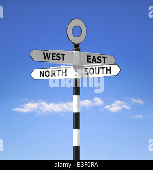 Direction signpost showing the compass points North South West and East against a bright blue sky - Stock Photo